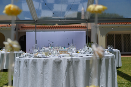 Catered service and tables ready for celebrating food eating event reception, busy light background Stock Photo