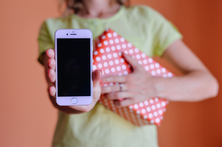 package sending: Portugal Europe - August 01, 2016: Happy woman holding Apple Iphone 6 mobile phone and parcel deliveries, light orange background