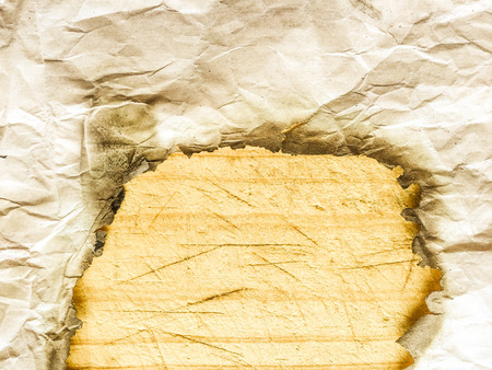 torn: Closeup on abstract burned crumpled paper, textured empty copyspace wooden table background