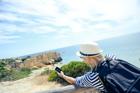 Woman on the beach holding smartphone camera in hands, taking photo. Back view on natural sunny outdoors background. Recreational exploration photography enjoyment activity