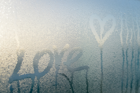 Love heart drawing on fogged glass surface light background. Emotional sensual feeling Stock Photo