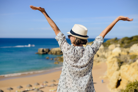 Back view of joyful amazed woman looking at the ocean natural outdoors background. Nice sunny morning seasonal travel vacation walk. Relaxing lifestyle Stock Photo