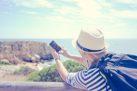 Back view of joyful amazed woman looking at the ocean natural outdoors background taking photography pictures. Nice sunny morning seasonal travel vacation walk. Relaxing lifestyle