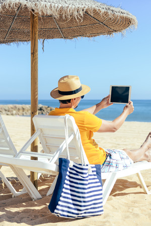 Back view of tourist using tablet pc on the beach. Holiday relaxation vacation photography on sunny blue sky seacoast, sea shore outdoors background