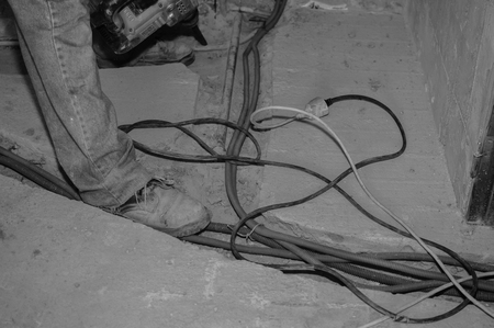 wooden floors: Building construction site and feet of a worker wearing boots on gray dusty concrete background