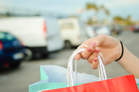 Closeup of woman hand holding shopping bags on the street copy space outdoors background. Modern lifestyle