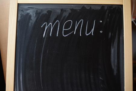 Closeup of menu writing on dark background copy space Stock Photo