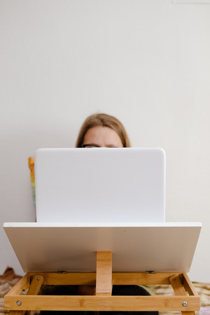Closeup view on woman working on laptop light background. Busy modern lifestyle