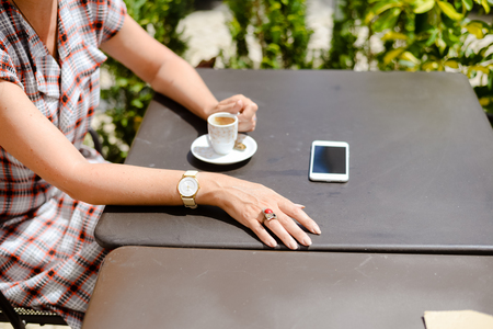 s video: Top side view of woman using smartphone, coffee table background. Closeup lifestyle photography, businesswoman and marketing application Stock Photo