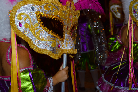 theatre masks: Pretty carnival costumes and feathers of unrecognizable dancers at night time festive background