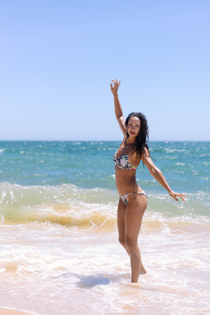 Attractive woman on a sunny summer holiday, coastal outdoors background. Travel lifestyle enjoying the sun on beach shore.