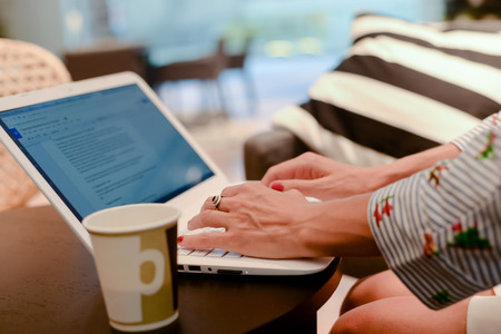 input device: Close up of defocused businesswoman hand busy typing on laptop light background, drinking coffee. Top side view, copy space photography. Social connection network, communication technology Stock Photo