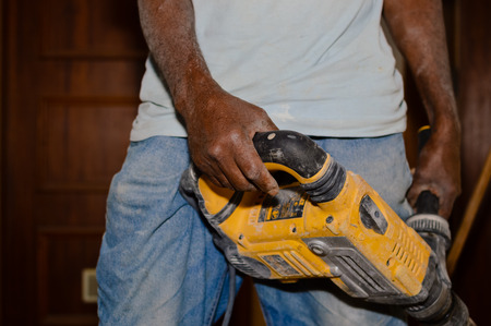 making hole: Closeup on busy man with electric drill over building background