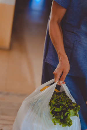 Close up on person holding bag from vegetables food market, abstract shopping background. Buyer seller business healthy lifestyle. Top side view