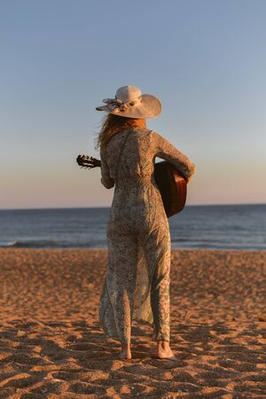 Attractive woman holding guitar on sunset sea beach outdoors background. Back side view of emotional walking female, instrumental relaxation