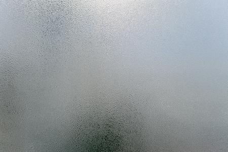 Das transparente unscharfe nebelige Glas des Fensters mit Kondenswasser lässt einfarbigen Hintergrund fallen. Vibrierende Frischeeinfachheitsbeschaffenheit, Jahreszeitstimmungsbild