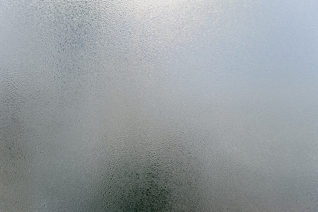 El vidrio de niebla borroso transparente de la ventana con agua condensada cae el fondo monocromático. Frescura vibrante simplicidad textura, imagen de humor de temporada