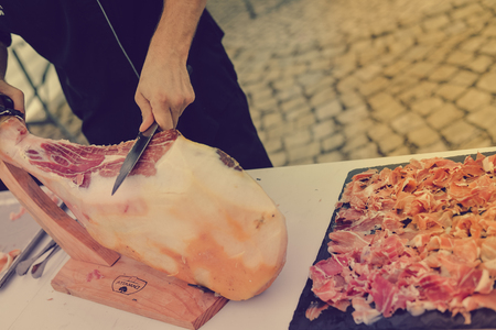 Dry cured ham thinly sliced. Closeup on chef hands in gloves slices prosciutto Italian delicatessen. Festive time background