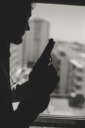 Black and white silhouette of a man holding a gun by the window background
