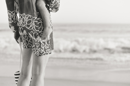 Closeup on mother and child legs by the beach shore outdoors tranquil nature background. Active caring female coastline walking, healthy beauty free leisure aspiration lifestyle scene. Back side view