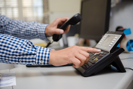 Close up of dialing a telephone device at office desk background, digital communication technology workplace. connection conference equipment group concept, happy professional telemarketer consulting 版權商用圖片