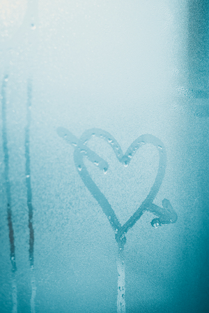 Love heart sign and foggy condensated window with blurry effect textured outdoors background, close up image 版權商用圖片