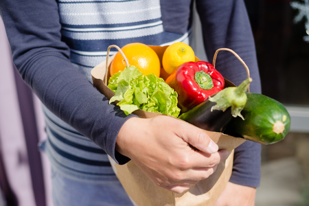 Person holding bag with healthy nutritious salad vegetables groceries on shopping market background, closeup top side view image