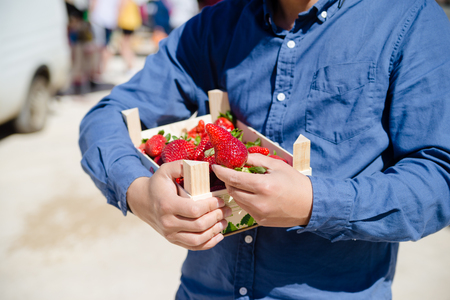 Person holding bag with healthy nutritious strawberries on groceries shopping market background, closeup top side view image Фото со стока