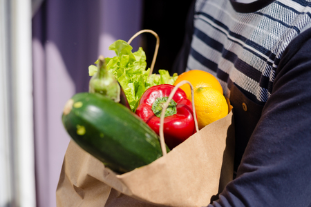 Closeup on person hand holding full bag of fruits and vegetables groceries, natural healthy shopping lifestyle