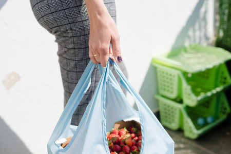 Woman holding bag with strawberries healthy nutritious food on groceries shopping market background, closeup top side view image