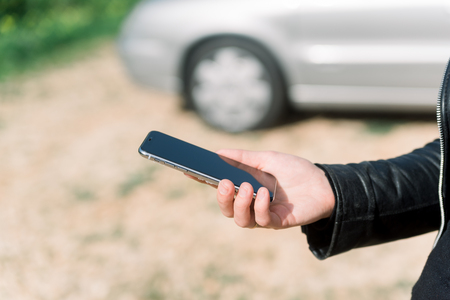 Woman using a mobile phone on car background, closeup image of social media, communication technology and busy lifestyle Stok Fotoğraf