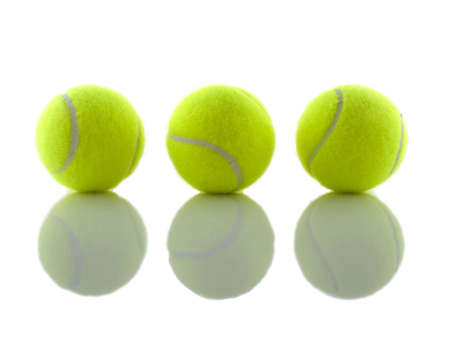 three tennis balls reflecting shadows on a mirror Stock Photo