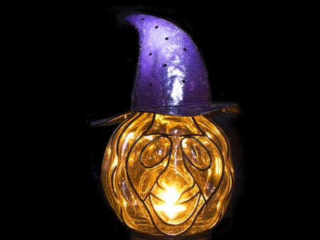 noteworthy: Pumpkin with a magic purple hat with a candle on a black background