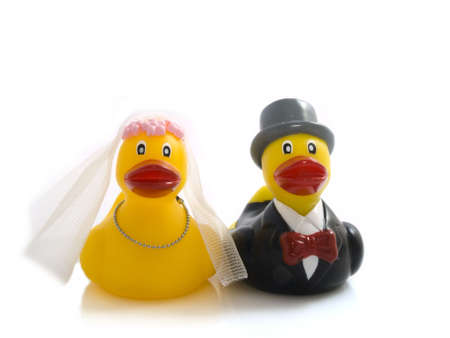 Two plastic ducks in a marriage outfit on a white background photo