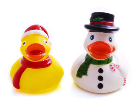 Two plastic ducks in christmas outfit on a white background photo