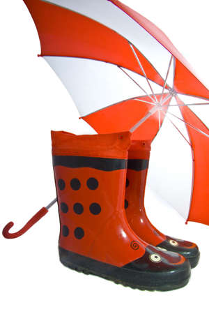 Rainboots and umbrella on a white background photo