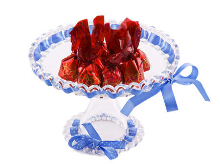 A bowl with cherry chocolate wrapped in red paper photo