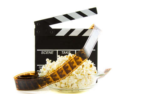 Clapper with popcorn and film isolated over white