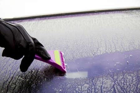 scraper: Cleaning the car window with a ice scraper