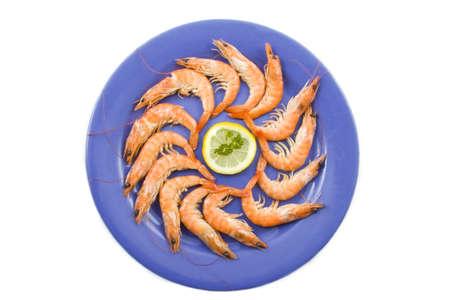 Verse garnalen op een blauw bord met citroen en peterselie