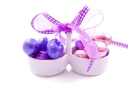 Basket with eggs and purple knot isolated over white
