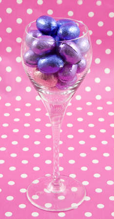Wine glass filled with easter eggs with speckled background photo