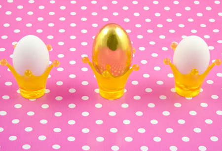 Two white eggs and one golden egg in crowncups on a speckles background photo