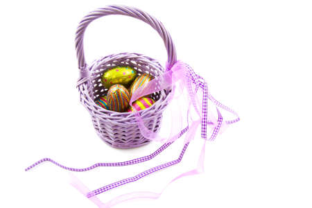 lint: Purple basket filled with chocolate eggs isolated over white
