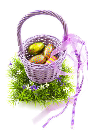 Purple basket filled with chocolate eggs on the grass isolated over white