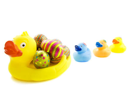 Mamma duck with chocolate eggs and three little ducks isolated over white photo