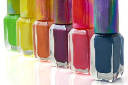 Colorful nailpolish in a row on a white background photo