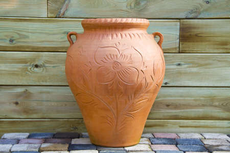 Big orange terracotta vase standing on stones on a wooden background photo