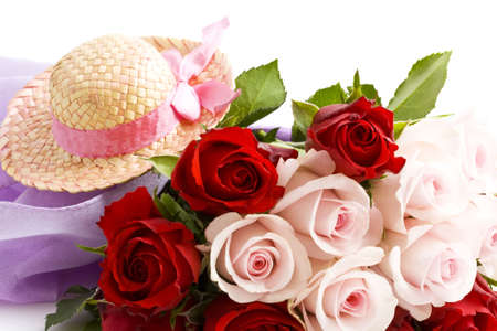 Red and pink roses with straw hat isolated over white photo