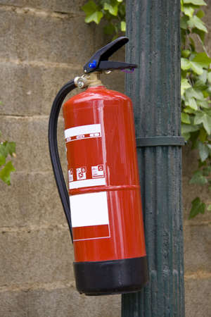 Fire extinguisher fixed on a pole in a nature surrounding photo